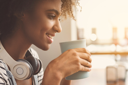 Positive modern girl is enjoying fresh coffee