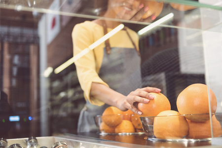 Friendly nice young woman is working in vegetarian shop