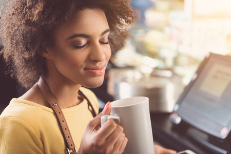 Pleasant young mulatto woman is relaxing with cappuccino at job Stock Photo