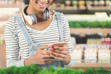 Joyful charming girl standing with smartphone in organic food store Stock Photo