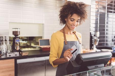 陽気な若い女性のキャッシャーがカフェで働いています。