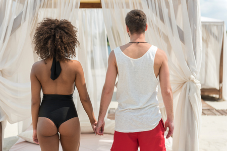 Young african lady in swimsuit and her boyfriend standing face to their cozy large sun bed hand in hand. Light curtains hanging over rest place. Focus on back