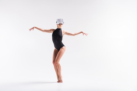 Somber youthful woman performing some dance from goggles video Stock Photo