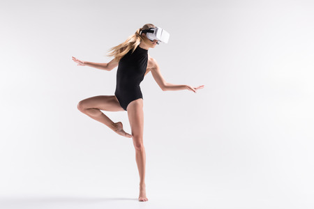 Thoughtful youthful sporty woman performing choreography using goggles Stock Photo