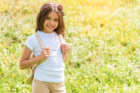 Joyful female kid walking on grassland with rucksack
