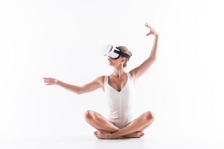 Serious young woman gymnast practicing yoga exercise through goggles Banco de Imagens - 83480952