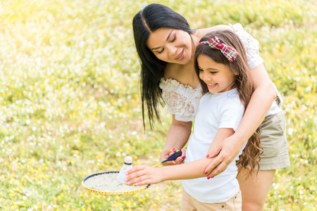 Happy girl learning tennis game with mother help
