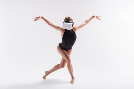 Youthful sporty woman simulating performance from video on goggles