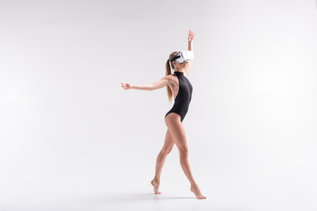 Serious youthful girl simulating sport composition using goggles Stock Photo