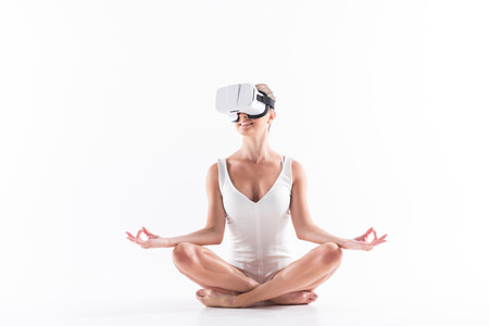 Jolly youthful sporty woman recreating with help of vr headset