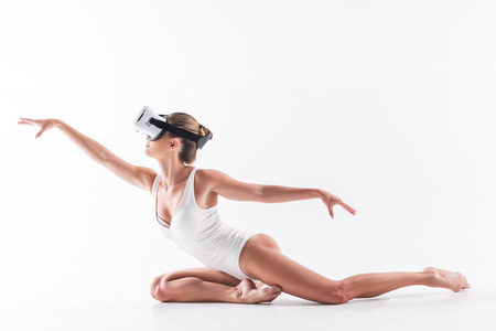 Solemn youthful girl exercising on floor with goggles on eyes