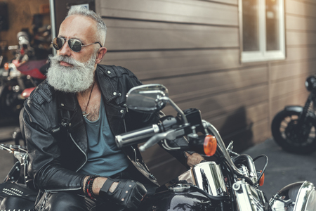Serious bearded old man on motorbike