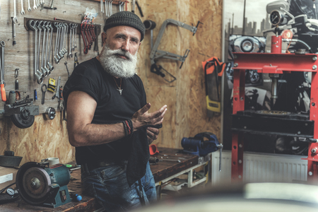 Geinteresseerde bebaarde volwassen man in werkplaats Stockfoto