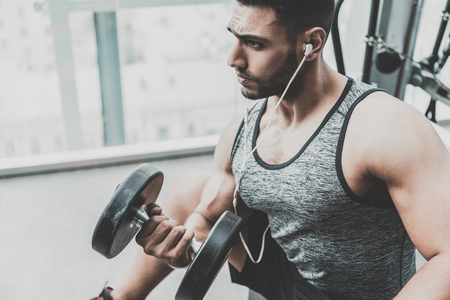 Serious bearded athlete lifting dumbbells