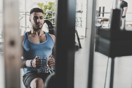 Serene unshaven man exercising in gym