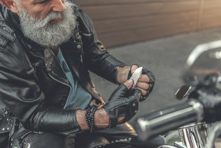 Attentive elder man working with sharp thing Banco de Imagens