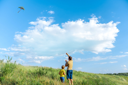 Cheerful man playing with his child on grassland