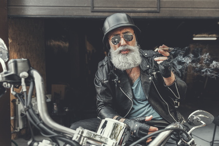 Elder bearded man having rest on bike Stock Photo