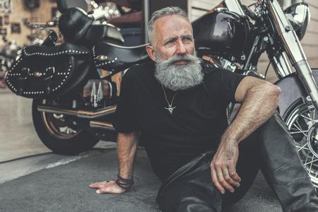 Dreamy old man locating near motorcycle 版權商用圖片