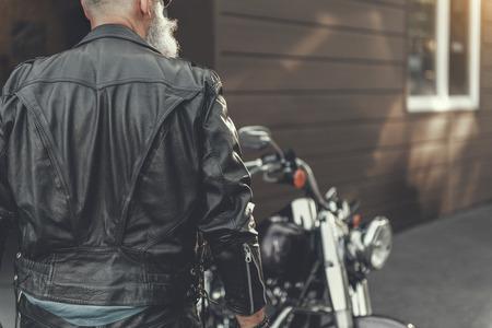 Mature man standing near motorbike