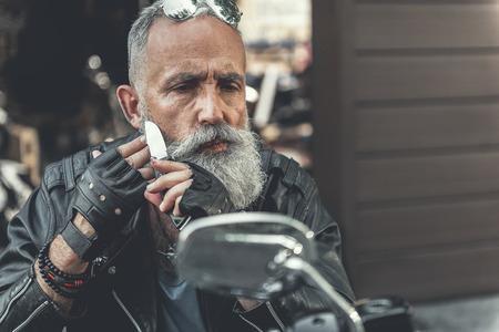 Thoughtful old bearded man shaving Banco de Imagens