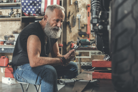 Serious old man in workshop