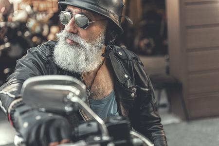 Serious mature man riding motorbike