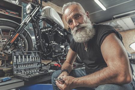 쾌활한 노인 오토바이 수리를위한 준비 스톡 콘텐츠