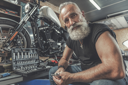 Cheerful old man ready for motorbike renovation Imagens