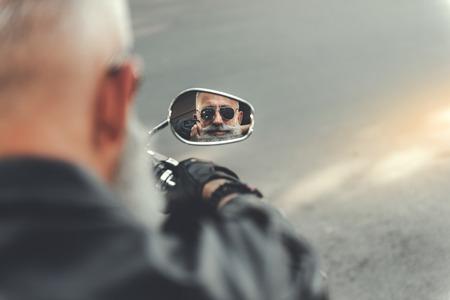 Serious elder man using motorbike