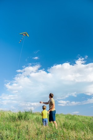 Carefree father and son launching kite on meadow