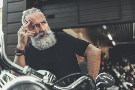 Mindful elder man locating on motorbike Banco de Imagens