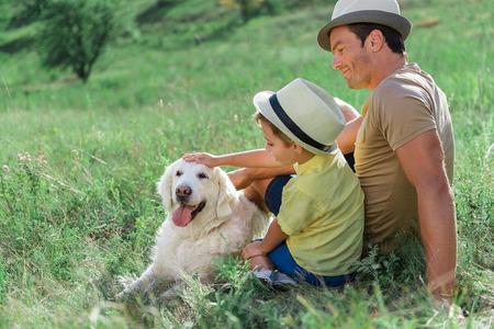 Happy parent and son stroking Labrador pet