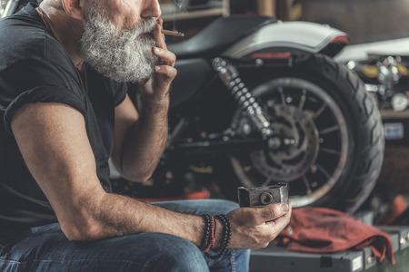 Old bearded man having some rest near bike