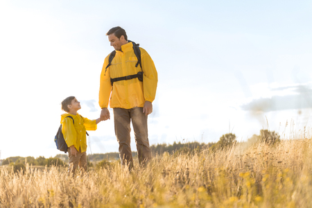 Happy father walking on meadow with his child Stock Photo