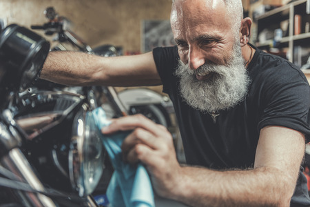 Happy smiling old man cleaning motorbike