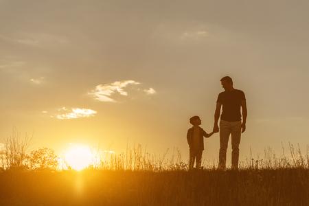 Friendly family walking on grass field together Standard-Bild