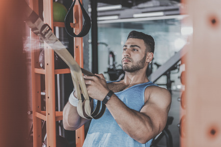 Serene male taking exercise in keep-fit studio