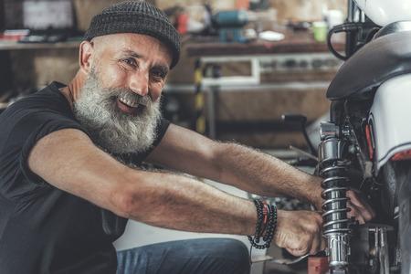 Cheerful smiling elder man in workshop