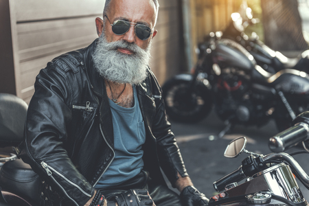 Old male person ready to ride motorbike