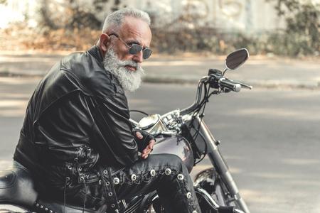 興味のある老人のオートバイに乗って準備ができて