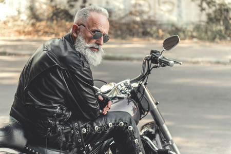Interested old man ready for riding motorcycle