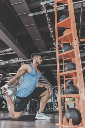 Serious bearded male taking physical exercise