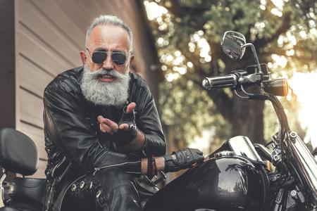 Glad elder male person using motorbike