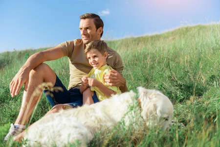 Carefree father and son spending time together on meadow Stock Photo