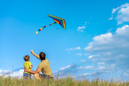 Cheerful boy and man playing with flying toy on field Stock Photo