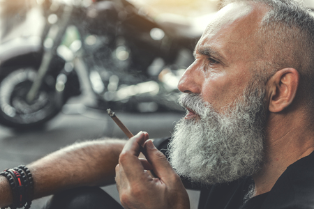 Serious old man keeping smoke
