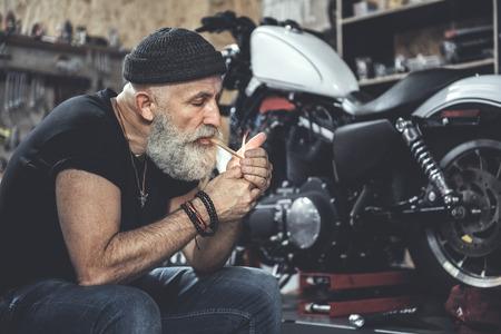 Busy old man smoking at workshop Stok Fotoğraf - 84013239