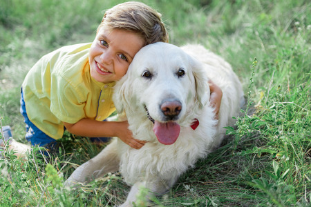 My best friend. Portrait of happy boy hugging his dog and smiling. He is looking at camera with happiness while kneeling on grass