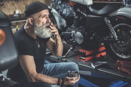 Thoughtful mature man smoking in garage